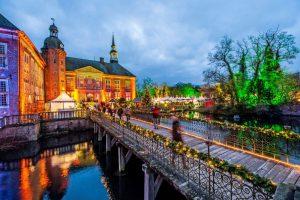 Vor dem illuminierten Wasserschloss Gödens spielen Jagdhornbläser weihnachtliche Lieder. Foto: djd/TMN/Schloss Gödens Entertainment